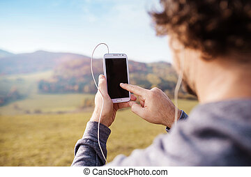 Young handsome runner with smart phone outside in sunny...