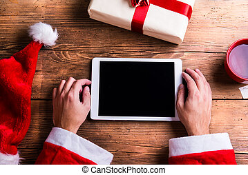 Santa Claus with tablet - Santa Claus holding tablet in his...