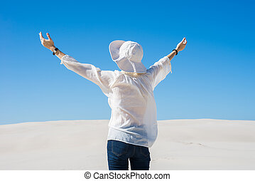 Woman lifting her hands up in the air standing on sand dune