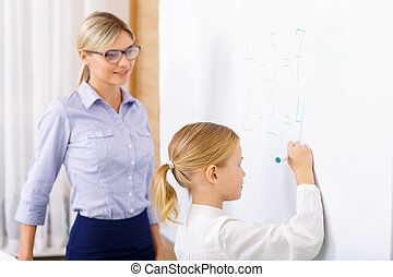 Teacher helps her pupil to solve basic equations.