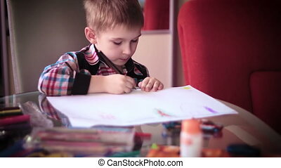Little boy sitting at table and drawing10 - Little boy...