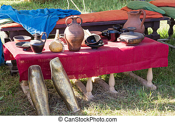 clay utensils on table with a red cloth coverings - clay...