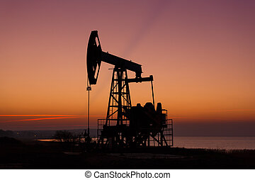 Oil derricks in sunset - Oil derricks on the background of...