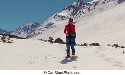Climber with snowshoes go against of snow-capped mountains