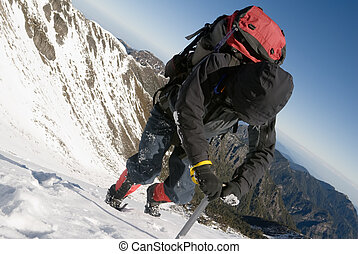 Mountain climber use ice axe to walk on snow ice slop in...