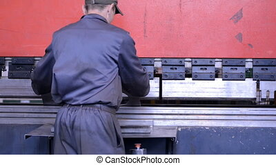 bend steel create a curved metal piece worker bending sheet...