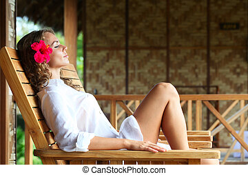 Woman relaxing on chaise lounge - Young beautiful woman...