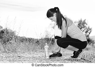 Attractive female runner tying her shoe laces