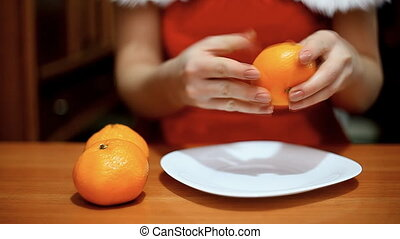 woman in suit Snow Maiden clears a tangerine