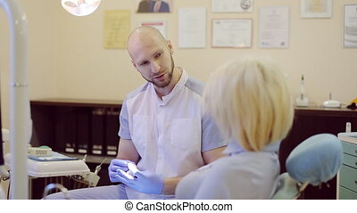 dentist tells the patient about teeth treatment - bald...