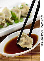 Steamed dumplings and soy sauce - Dumpling being dipped in...