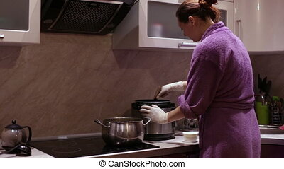 A woman stirs a pot spoon adds seasoning - A woman prepares...