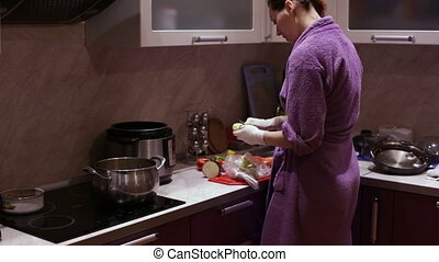 Woman in gloves cleans zucchini in the kitchen - Woman in...