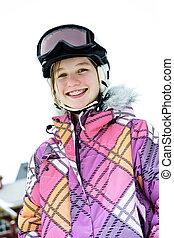 Happy girl in ski helmet at winter resort