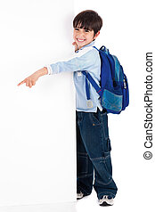 Young kid happily standing behind the board and pointing to...