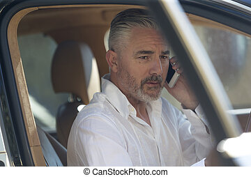 Quick call before driving to work - Businessman making a...