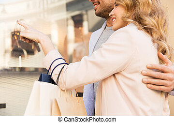 couple with shopping bags looking at shop window - sale,...