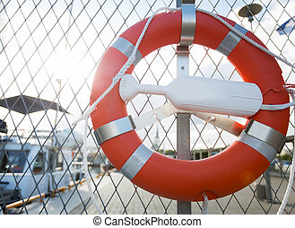 lifebuoy over moored boats on pier - sailing, safety and...