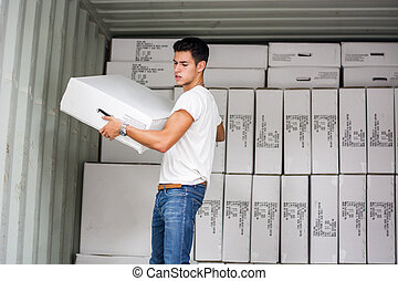 Young Man with Large White Box by Freight Train - Waist Up...