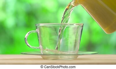 Aromatic tea pouring into glass cup - fresh aromatic tea...