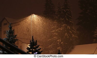 Snowing at night on the background of a lamppost - Snowfall...