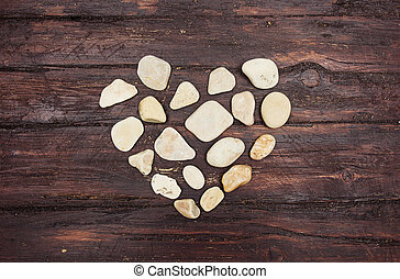 A heart shaped pebble stones on a old wood planks