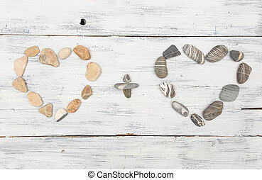 Two heart shaped pebble stones on a old wood planks