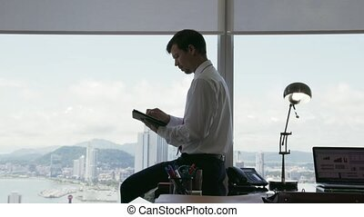 24 Person Using Tablet PC Looking Out Of Office Window -...