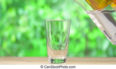 Clear water pouring from water filter on nature background