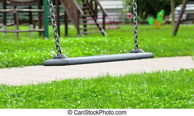 empty swing with chains swaying at playground for child,...