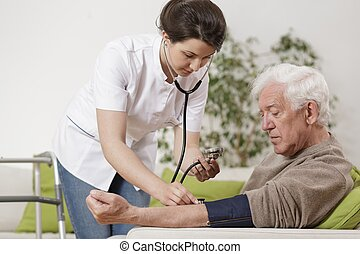 Young nurse taking blood pressure - Young nurse taking old...