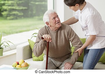 Man leaning on walking stick - Young woman helping old man...