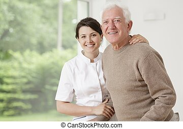 Woman caring for old man - Young nurse taking care of old...