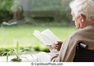 Old man reading a book - Old man on wheelchair reading a...