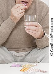 Old man taking tablet - Sick old man taking tablet with...
