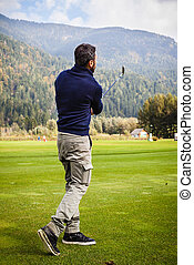 Playing golf near the mountains