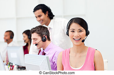 Portrait of an Asian customer agent and her team in a call...