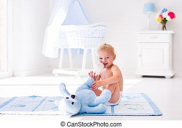 Baby boy with milk bottle in sunny nursery - Cute blond...