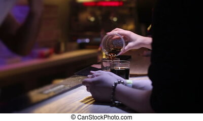 mixing whiskey with coke at nightclub on bar