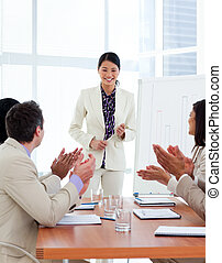 Successful asian woman giving a presentation in a company
