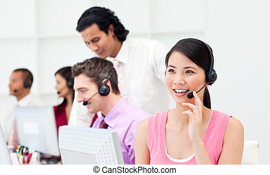Beautiful Asian customer agent and her team in a call center