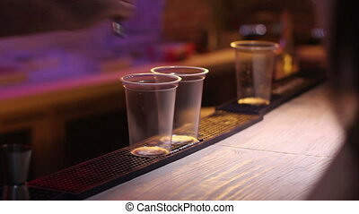 bartender puring two glasses of gin in nightclub