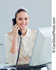 Enthusiastic businesswoman talking on phone in the office