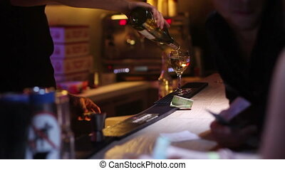 bartender puring glass of wine for women