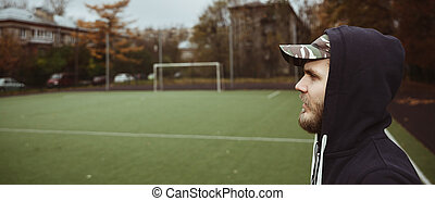 Muscular male athlete taking break standing relaxing after training