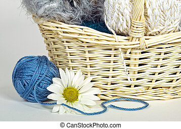 Leisure Time - Skeins of yarn with daisy and basket.