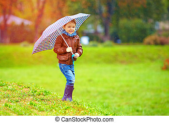 happy boy running under an autumn rain