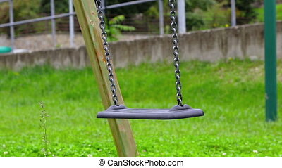 empty swing with chains swaying at playground for child, moved from wind, on green meadow background, hd 1080p