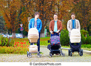 fathers walking with buggies in city park, parental leave