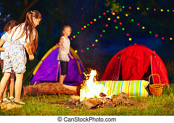 kids throwing wood in campfire, summer camp